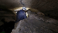 NWA Democrat-Gazette/DAVID GOTTSCHALK  Guy Schiavone, general manager and guide, is illuminated by a headlamp and flashlight Tuesday, October 11, 2016, as he squeezes through a crevice while  leading a tour on the Wild Tour of War Eagle Cavern on Beaver Lake. The Wild Tour gives visitors a guided realistic experience of spelunking that requires helmets, lights, gloves, knee pads and the willingness to get muddy and possibly wet.