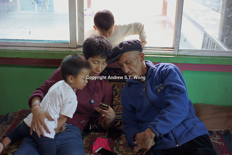 Diqing Tibetan Autonomous Prefecture, Yunnan Province, China - Members of a Tibetan family check out a mobile phone, August 2018.