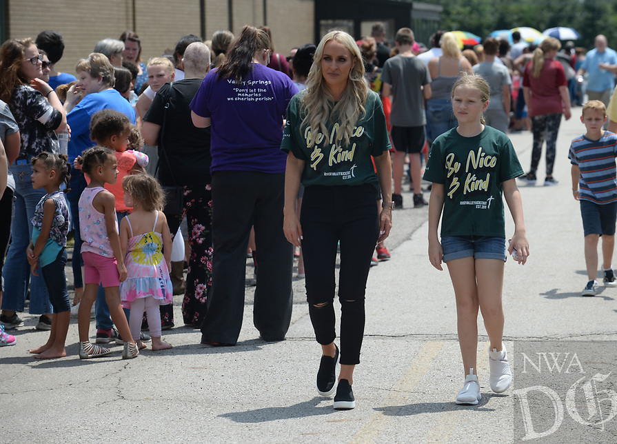 NWA Democrat-Gazette/ANDY SHUPE<br /> Carrie Jernigan (center) and her daughter, Harper, 9, survey the length of the line of residents Saturday, Aug. 10, 2019, as they wait outside in the heat during the River Valley Kick Start at Alma Middle School. Inspired by her daughter, Harper, Jernigan bought all 1,500 pairs of shoes from a closing Payless Shoe Source in Fort Smith. Her effort national publicity and thousands of dollars in donations, which she used to buy more shoes and school supplies for kids going back to school.