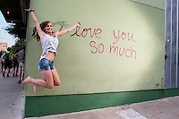 "An Austin local woman jumps for joy at the ""i love you so much"" mural on South Congress Avenue, Austin, Texas."