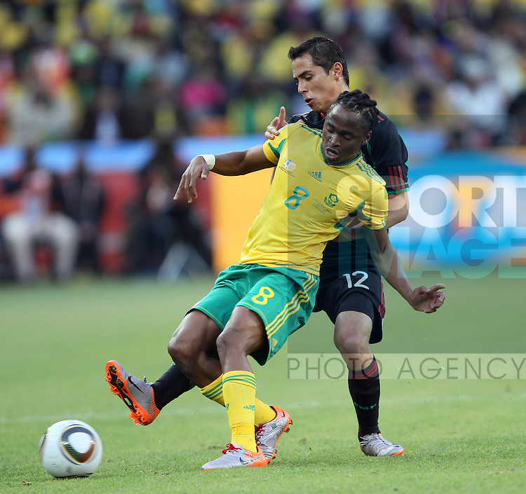 South Africa's Siphiwe Tsahabalala tussles with Mexico's Paul Aguilar