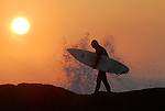 Surfer at Lighthouse Pt. at sunset
