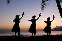 Three hula dancers at Olowalu, Maui, framed by palm trees.