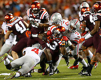 Ohio State Buckeyes linebackers Jerome Baker (4) and Dante Booker (33) and safety Vonn Bell (11) team up to tackle Virginia Tech Hokies safety Der'Woun Greene (23) during Monday's NCAA Division I football game in Blacksburg, Va., on September 7, 2015. Ohio State won the game 42-24. (Dispatch Photo by Barbara J. Perenic)