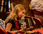 "July 26, 2017. Raleigh, North Carolina.<br /> <br /> Allí Lambert, age 12, checks out copies of two of Alan Gratz's books.<br /> <br /> Author Alan Gratz spoke about and signed his new book ""Refugee"" at Quail Ridge Books. The young adult fiction novel contrasts the stories of three refugees from different time periods, a Jewish boy in 1930's Germany , a Cuban girl in 1994 and a Syrian boy in 2015."