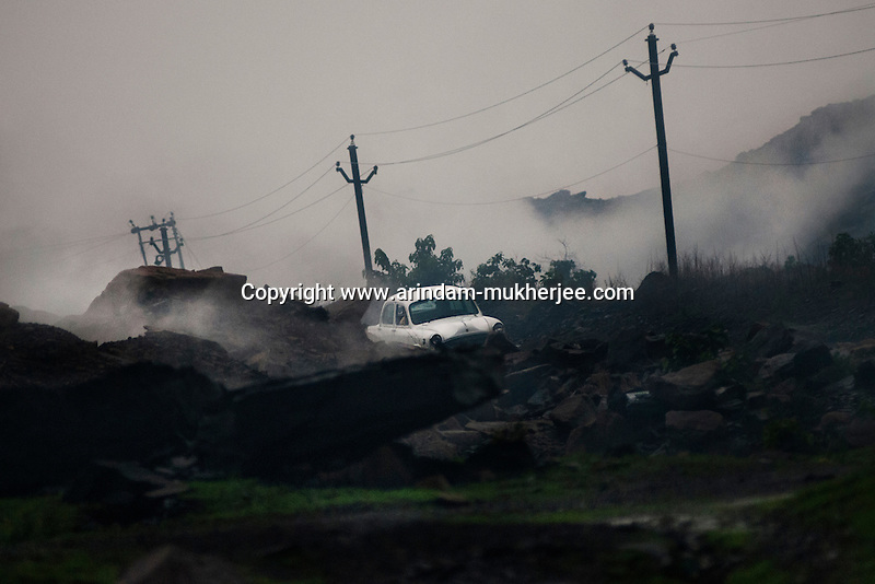A car passes through the poisonous gases and fumes generating from burning coal seam beneath the surface. The roadways are also affected in and around Jharia. Government is trying to divert these roads through safe lands. A huge coal mine fire is engulfing the city of Jharia from all its sides. All scientific efforts have gone in vain to stop this raging fire. This fire is affecting lives of people living in and around Jharia. Jharkhand, India. Arindam Mukherjee