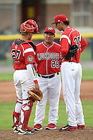 Batavia Muckdogs pitching coach Brendan Sagara (28) talks with catcher Rodrigo Vigil (27) and pitcher Jorgan Cavanerio (35) during a game against the Auburn Doubledays on June 16, 2014 at Dwyer Stadium in Batavia, New York.  Batavia defeated Auburn 4-3.  (Mike Janes/Four Seam Images)