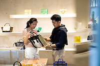 HONG KONG - MAY 04: Patricia Szeto and Jonathan Lui shop for a handbag in a fashion store in Landmark shopping mall in Central business district, on May 4, in Hong Kong. (Photo by Lucas Schifres/Pictobank)