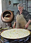 Palestinian baker prepares Nabulsi Kunafa, a traditional and favorite local sweet, in the West Bank, city of nablus on May 24, 2012. Photo by Nedal Eshtayah  .
