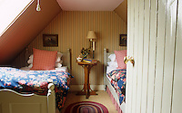 The cosy twin attic bedroom is decorated in a variety of patterns from the striped wallpaper to the floral duvet covers