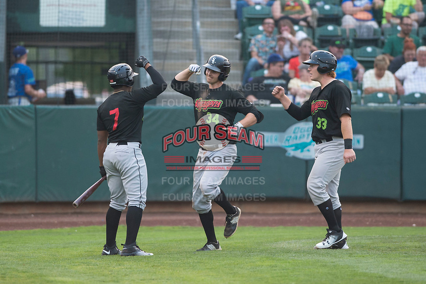 Great Falls Voyagers first baseman Ryan Fitzpatrick (34) is congratulated by Maiker Feliz (7) and Gunnar Troutwine (33) after hitting a home run during a Pioneer League against the Ogden Raptors at Lindquist Field on August 23, 2018 in Ogden, Utah. The Ogden Raptors defeated the Great Falls Voyagers by a score of 8-7. (Zachary Lucy/Four Seam Images)