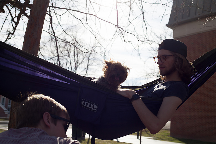 Evan Leonard and Clover the dog lay in a hammock with the Hammock Club outside of Morton Hall on February 24, 2017.