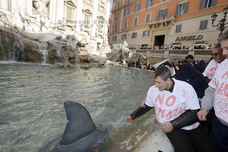 Roma, 17 Novembre 2012.Fontana di Trevi.Flash mob dell'associazione Mare Vivo contro il taglio delle pinne di squalo..Una pinna in acqua , magliette insanguinate e pinne in testa degli attivsiti