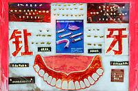 Sign outside street dentist offering choices for lost teeth, Barkhor, Lhasa, Tibet.