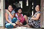 Three young women share a laugh with passersby in Hue, Vietnam.