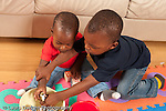Three year old boy playing with toys and 12 month old baby brother grabbing brother's arm and putting toy out of his hand horizontal