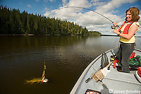 Woman landing a northern pike