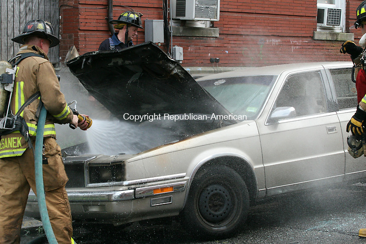 TORRINGTON, CT - 13 August, 2009 - 081309MO01 - Torrington firefighters made quick work of a car fire on Linden Street reported shortly after 4 p.m. Thursday. Sheryl Stanchfield, the owner of the damaged Chrysler New Yorker seen here, said she had just returned from a shopping trip, walked inside her home for a moment, and came out to find smoke billowing from under the hood. Stanchfield attempted to extinguish the blaze herself without success. The cause of the fire was under investigation. Police blocked off South Main Street for several blocks for about 15 minutes while firefighters put the fire out. Jim Moore Republican-American.