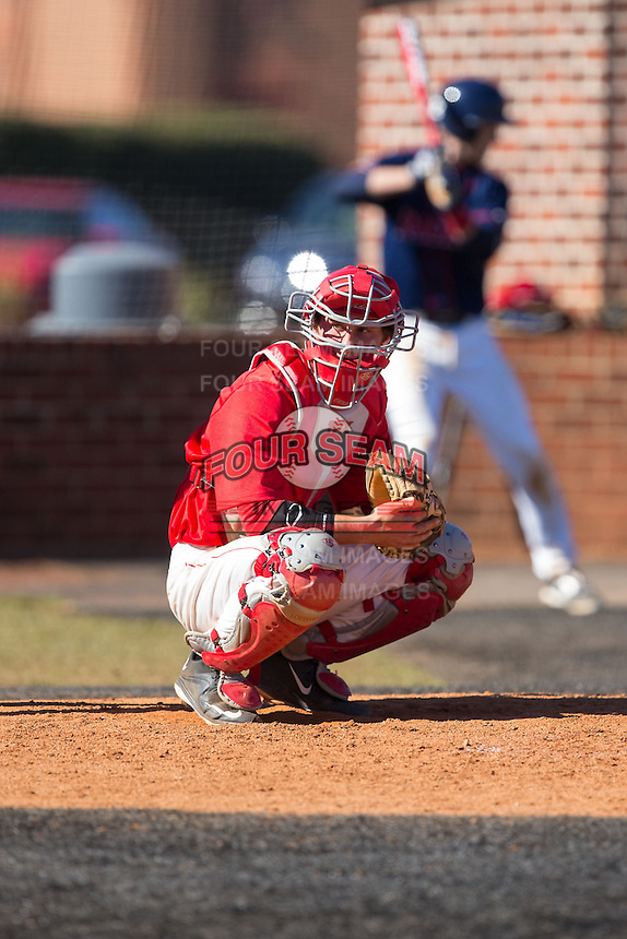 Belmont Abbey Crusaders catcher Drew Sipp (5) looks to the dugout for the pitch call during the game against the Shippensburg Raiders at Abbey Yard on February 8, 2015 in Belmont, North Carolina.  The Raiders defeated the Crusaders 14-0.  (Brian Westerholt/Four Seam Images)