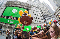 "Hordes of visitors clammer for free balloons with faces representing Line ""stickers"" in front of the New York Stock Exchange decorated for the Japanese messaging company Line's initial public offering on Thursday, July 14, 2016. Line Corp., a popular messaging app in Japan is owned by South Korean Naver Corp. Line has 218 million active users monthly, with Japan, Taiwan and Indonesia accounting for two-thirds of them.   (© Richard B. Levine)"
