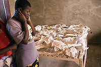 Rwanda. Southern province. Murambi. A young woman cries while looking at the skeletons of Tutsis, killed during the 1994 genocide. Mortal remains laid on wood boards at the Genocide Memorial. Over 50'000 people perished on the site and thrown in mass graves. The site of Murambi is located in the district of Nyamagabe, in the former Gikongoro prefecture, Nyamagabe commune. The site of Murambi is intented to be a regional research and documentation centre on Genocide. A special memory place. © 2007 Didier Ruef