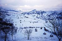 ROMANIA / Maramures / Valeni / January 2003..A winter landscape of fields and haystacks looking towards the village of Barsana in the neighboring Iza valley...© Davin Ellicson / Anzenberger