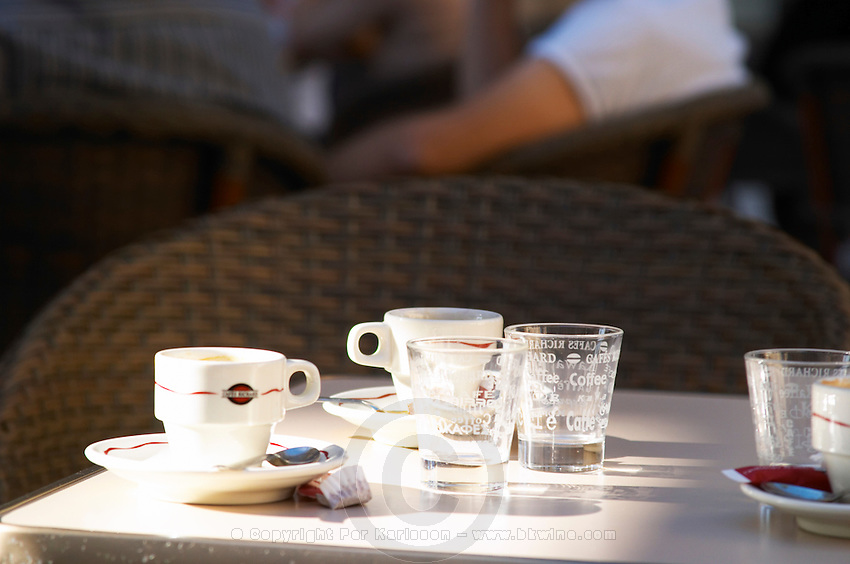 An outside cafe terrasse table in Bordeaux with empty coffee cups expresso espresso and water glasses in the sun
