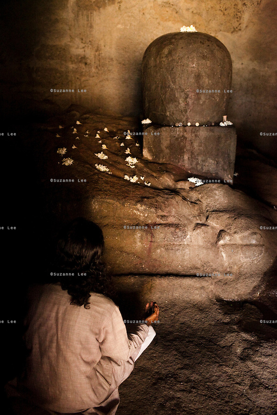 Indian tourists praying to Shiva Lingam in the Elephanta Caves, a Hindu place of worship for the Lord Shiva, accessible by a long ferry ride in the Arabian sea, Mumbai, India. Photo by Suzanne Lee