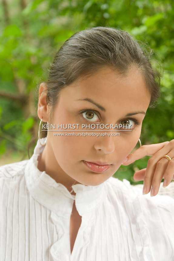 Extreme closeup of a beautiful young brunette woman looking directly into camera.  Shallow depth-of-field with eye and lips in sharp focus.