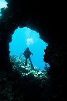 scuba diver looking into swim-through hole on lava rock, Lanai, Hawaii, USA, Pacific Ocean, MR