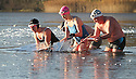 """02/12/12 ..Blue swimsuit: Lucy Petrie (46), Black swimsuit: Karen Mellstrom (40), black hat: Brendan Massam (45), white hat: Nils Johnson. ..After sub-zero overnight temperatures, members of the Frensham Aquatic Recreational Team (FARTs) clear ice from the surface of Frensham Great Pond near Farnham Surrey, before braving the water for eight and a half minutes. The newly formed group swim in the lake two or three times each week, and this is the first time they have had to break the ice before their morning dip...""""It makes you feel euphoric for the day - although you do shake for a while when it is this cold. It takes several hours for your core temperature to warm up"""" said Lucie Petrie after emerging from the frigid water which was a 'balmy' 4 degrees beneath the ice...All Rights Reserved - F Stop Press.  www.fstoppress.com. Tel: +44 (0)1335 300098."""