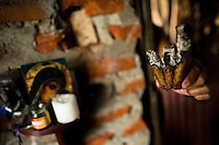 A Colombian urban shaman (brujo) shows three burning cigars while predicting the future from shapes shown on the tobacco leaves in his house in Cali, Colombia, 17 April 2013. Although the original spiritual tradition, kept by the indigenous shamen in Americas for centuries, has been systematically repressed by the Catholic Church, nowadays, more and more people from the urban areas of Latin America discover their roots and consult their everyday problems with esoteric practitioners, healers and shamen. Traditional indigenous rituals (reading of tobacco - interpretation of signs shown by burn tobacco leaves) have merged with European concepts (divination using playing cards) and animistic religious beliefs (worshipping the spirits) brought to Americas by the African slaves, keeping the spirituality in modern Latin American society alive.