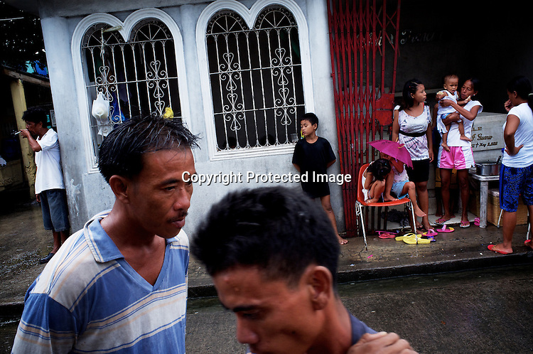 The local residents seen sheltering from the rain and around the graveyards at the Manila North Cemetery in Manila, Philippines. The scarcity of land and ever growing population has led the local filipinos to live in the same space around the graveyards in the Cemetary. Photo: Sanjit Das