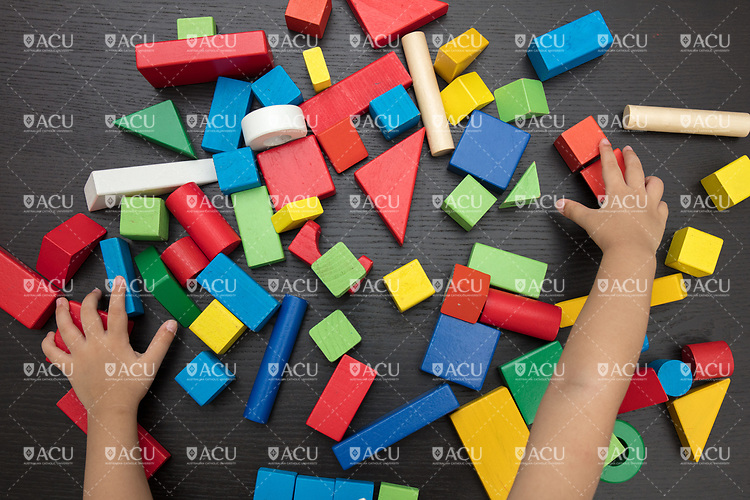 Aerial view of child's hand close up playing building blocks