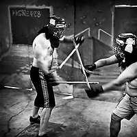 Two men fight using sticks in a garage on a fight night. 'Gentlemen's Fight Clubs' are held in private garages or homes. People who work as software engineers and programmers during the day meet there to fight. This way they are able to let out their tensions, frustrations and passions in somtimes overtly violent ways. The participants are known to use keyboards, dustbusters and rolled up women's magazines in their fights. Silicon Valley, California.