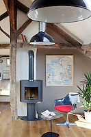 Under the ancient attic beams of the living room an antique map hangs next to a modern wood burning stove