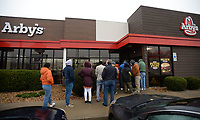 A line of people forms Saturday, Jan. 11, 2020, in the cold outside the Arby's restaurant on Martin Luther King Jr. Boulevard in Fayetteville as they vie to win free food for a year. Nine restaurants in Bentonville, Rogers, Lowell, Springdale, Fayetteville, and Siloam Springs celebrated their remodeling with a customer appreciation day, offering free food for the first 25 patrons present at each location's opening as well as $1 sandwiches all day. First in line was Abud Metwally, a MFA student at the University of Arkansas from Egypt, who arrived at dawn. Check out nwaonline.com/200112Daily for today's photo gallery. (NWA Democrat-Gazette/Andy Shupe)