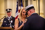 WATERBURY, CT. 20 December 2019-122019BS246 - Jennifer Ballou, left, pins the gold badge, as Waterbury Fire Chief, on her husband's Terry Ballou uniform, during the swearing in ceremony for Waterbury Fire Chief at City Hall on Friday. Terry Ballou replaces former Fire Chief David Martin, who retired earlier this year. Bill Shettle Republican-American