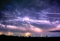 """""""Anvil Crawler"""" a form of cloud-to-cloud lightning, splays it's raw power across the night sky east of Norman Oklahoma on July 7th, 1994."""