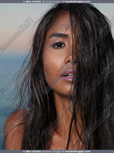 Sensual beauty portrait of a young woman with long wet dark hair covering half of her face with sunset sky in the background.