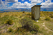 The Southland Ski Club hut outside toilet (dunny, or outhouse) high above the Mataura valley with the Eyre Mountains in the distance, Southland District, Southland, South Island, New Zealand.