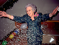 Grandmother age 82 celebrating with glitter at wedding reception.  St Peter  Minnesota USA