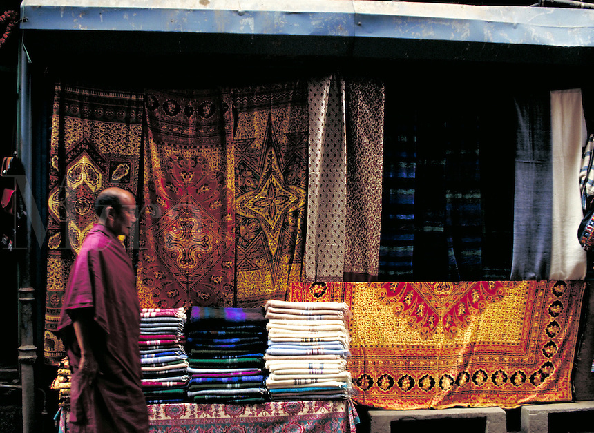 Monk in purple robe passes shop with brightly colored textiles hung on wall or folded and stacked. Kathmandu, Nepal.