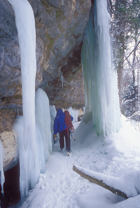 An ice climber in Pictured Rocks National Lakeshore near Munising, Mich. carries his ropes past ice formations after a day of climbing.