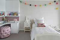 A young girl's bedroom has a painted single bed and built-in storage unit with dressing table. Small touches of pink add spots of colour to the otherwise white room.