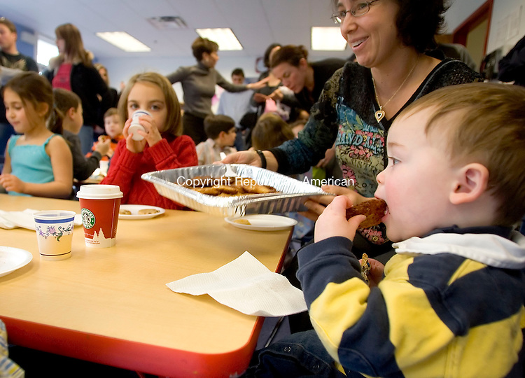SOUTHBURY, CT- 17 DEC 06- 121706JT03- <br /> Bennett Samberg, 19 months, bites into a latke given to him by Ellen Martino during a celebration of Chanukah at the B'nai Israel Religious School on Sunday at the Walzer Family Jewish Community Center Campus in Southbury.<br /> Josalee Thrift Republican-American