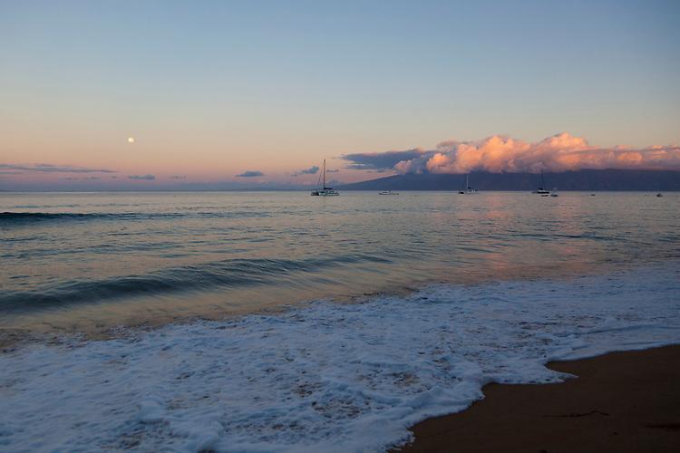 Full moon over Ka'anapali Beach, Maui, Hawaii. The island of Molokai is visible in the distance.