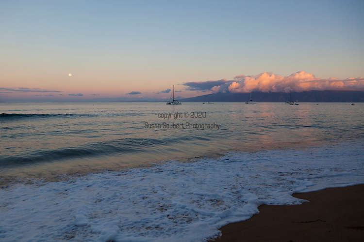 Full moon over Ka'anapali Beach, Maui, Hawaii. The island of Molokai is visible in the distance.