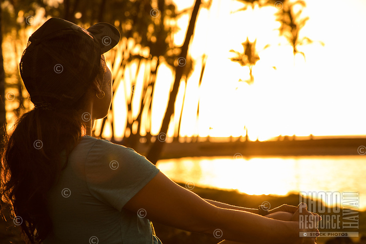 A woman looks towards Ku'uali'i Fishpond and the ocean at sunset, 'Anaeho'omalu Bay, Big Island of Hawai'i.