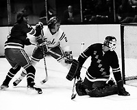 Seals Stan Weir watches goal, Rangers Ron Greschner and goalie Ed Glacomin. (1974 photo /Ron  Riesterer)